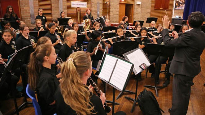 Students in the band performing in the school hall.