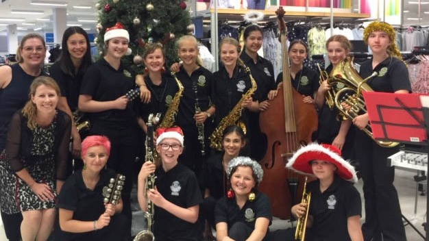 Band students and teachers at Kmart store dressed with Christmas accessories in front of Christmas tree