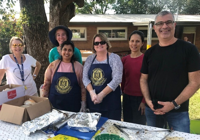 Parents in aprons working on the BBQ stall in the playground